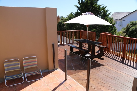 Suite 5 Balcony leading to Wooden Guest Deck with Picnic Tables and Umbrellas.